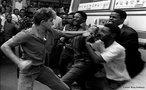 A política de segregação racial tornou-se oficial em 1948 na África do Sul. Em 1960, a polícia matou 67 negros que participavam de uma manifestação. O Massacre de Sharpeville, como ficou conhecido, provocou protestos em diversas partes do mundo. Como consequência, a CNA foi declarada ilegal, seu líder, Nelson Mandela, foi preso em 1962 e condenado à prisão perpétua. <br><br/> Palavras-chave: relações de poder, relações culturais, apartheid, Nelson Mandela.
