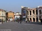 A Piazza Bra � maior pra�a de Verona e seu nome � origin�rio do termo braida que, por sua vez, deriva do alem�o breit, ou seja, largo, amplo, um vasto espa�o. E de fato � uma pra�a grande e abriga diversos pal�cios, casas e monumentos de �pocas muito diferentes entre si, desde a Antig�idade Romana at� o s�culo XIX. � esquerda da pra�a, para quem chega dos Portoni della Bra, vemos o Teatro Filarmonico, cuja constru��o iniciou-se em 1716 e conclu�do somente em 1729, sendo destru�do quase completamente durante a II Grande Guerra e reconstru�do de acordo com o projeto inicial. Do outro lado da rua, vemos fileiras de casas coloridas com toldos verdes que abrigam restaurantes e bares de p�blico mais seleto, ao centro, uma grande �rvore e um pequeno chafariz, ao fundo, a imponente Arena, um dos s�mbolos da cidade e heran�a dos nossos ancestrais romanos, � direita, o edif�cio do Munic�pio de Verona e o Palazzo della Gran Guardia, constru�do no in�cio de 1610 e conclu�do na metade do s�culo XVIII. <br><br/> Palavras-chave: It�lia, arquitetura, Verona, arte renascentista.